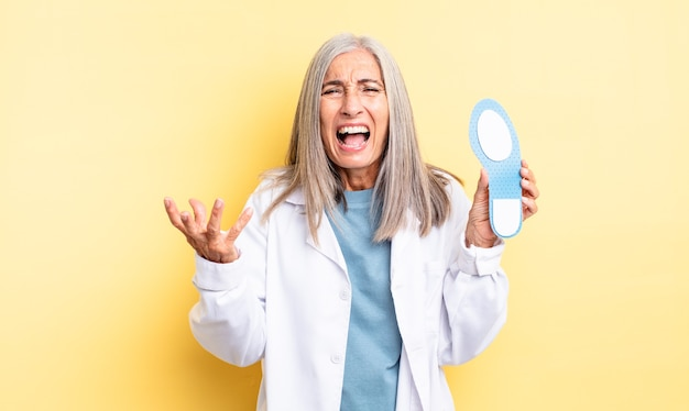Middle age pretty woman looking angry, annoyed and frustrated. chiropodist concept