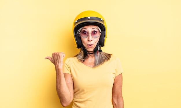 Симпатичная женщина среднего возраста выглядит удивленно в недоумении. концепция мотоциклетного шлема