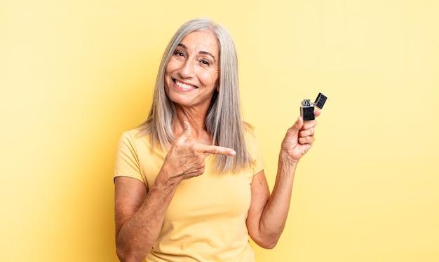 興奮して驚いた中年のきれいな女性が横を指しています。軽いコンセプト