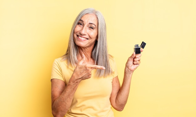Middle age pretty woman looking excited and surprised pointing to the side. lighter concept