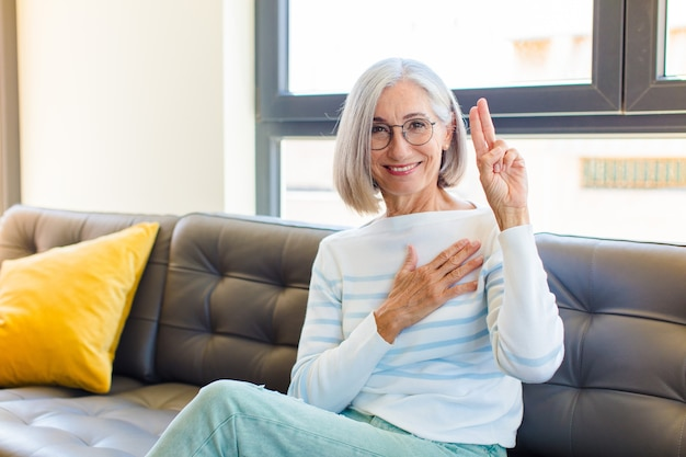 Middle age pretty woman looking happy, confident and trustworthy, smiling and showing victory sign, with a positive attitude
