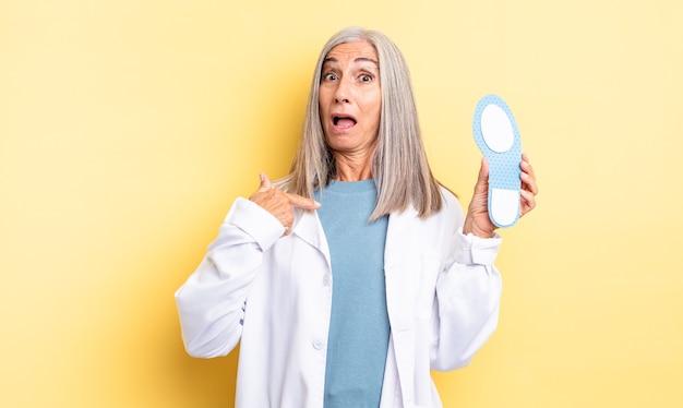 Симпатичная женщина среднего возраста выглядит шокированной и удивленной с широко открытым ртом, указывая на себя. концепция хиропода