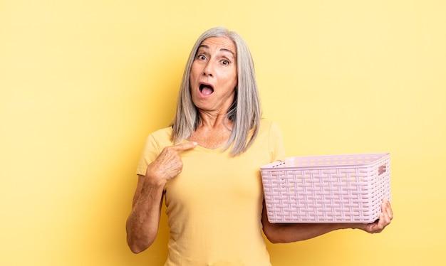 Симпатичная женщина среднего возраста выглядит шокированной и удивленной с широко открытым ртом, указывая на себя. концепция пустой корзины