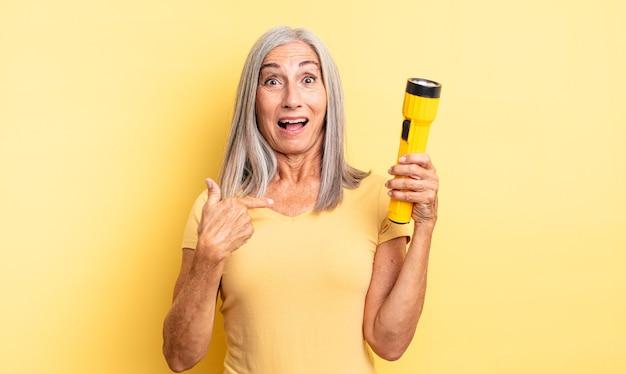 중년의 예쁜 여성은 자신을 가리키며 입을 크게 벌리고 놀란 표정을 짓고 있습니다. 손전등 개념