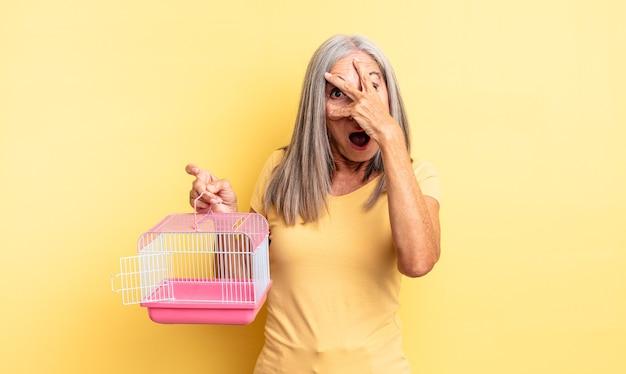 중년의 예쁜 여성은 충격을 받거나 무서워하거나 겁에 질려 손으로 얼굴을 가리고 있습니다. 애완 동물 케이지 또는 감옥 개념