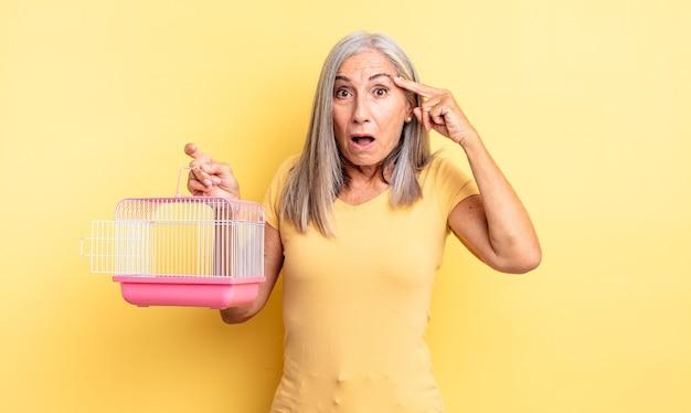 새로운 생각, 아이디어 또는 개념을 깨닫고 놀란 중년의 예쁜 여성. 애완 동물 케이지 또는 감옥 개념