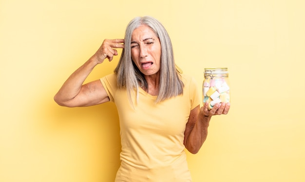 不幸でストレスを感じている中年のきれいな女性、銃のサインを作る自殺ジェスチャー。キャンディーボトルのコンセプト