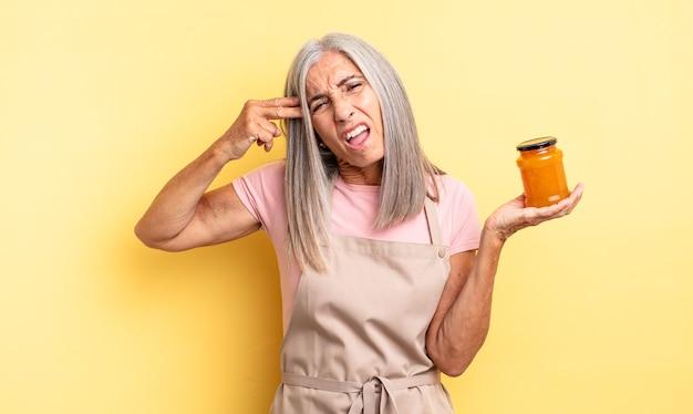 Симпатичная женщина среднего возраста, выглядящая несчастной и подчеркнутой, жест самоубийства, делая знак пистолета. персиковое варенье