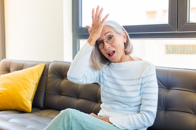 Симпатичная женщина среднего возраста, поднимающая ладонь ко лбу, думает, ой, после глупой ошибки или вспоминая, чувствуя себя немой