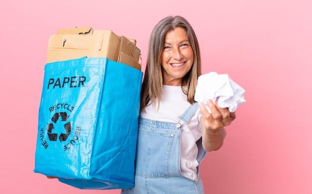 Красивая женщина среднего возраста перерабатывает бумагу