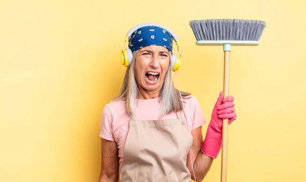 Симпатичная женщина среднего возраста агрессивно кричала, выглядела очень сердитой. концепция домашнего хозяйства и метлы