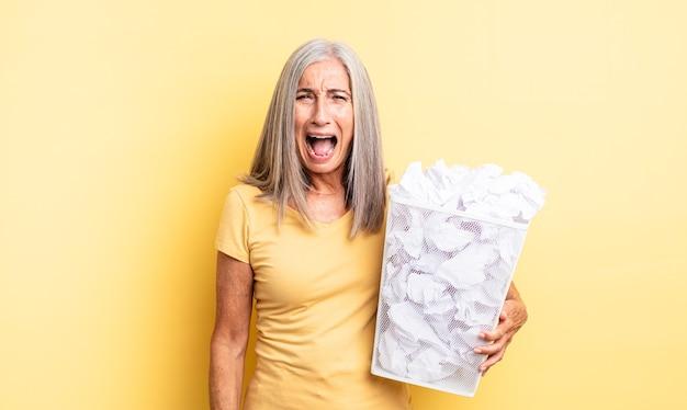 Симпатичная женщина среднего возраста агрессивно кричала, выглядела очень сердитой. концепция провала бумажных шаров