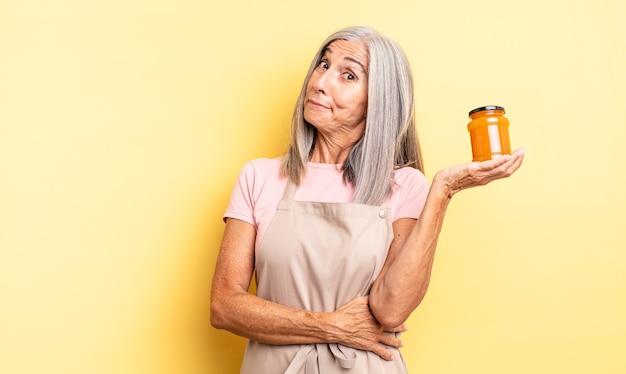 Симпатичная женщина средних лет пожимает плечами, чувствуя смущение и неуверенность. персиковое варенье