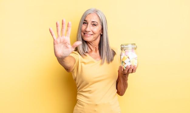 中年のきれいな女性が笑顔でフレンドリーに見え、5番目を示しています。キャンディーボトルのコンセプト