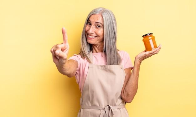 Симпатичная женщина среднего возраста улыбается и выглядит дружелюбно, показывая номер один. персиковое варенье