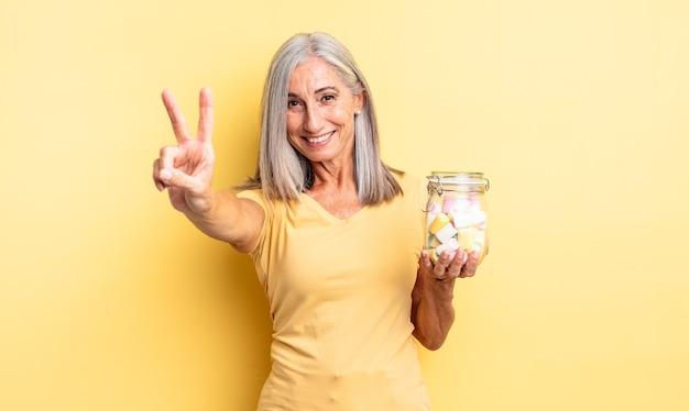 笑顔と幸せそうに見える中年のきれいな女性、勝利または平和を身振りで示す。キャンディーボトルのコンセプト