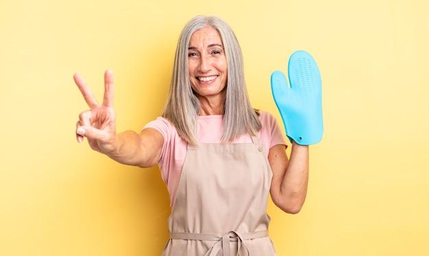 Симпатичная женщина среднего возраста улыбается и выглядит счастливой, показывая победу или мир. концепция рукавицы духовки