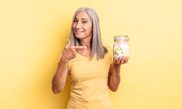 元気に笑って、幸せを感じて、横を指している中年のきれいな女性。キャンディーボトルのコンセプト