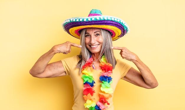 自信を持って笑顔を浮かべる中年のきれいな女性が自分の広い笑顔を指しています。メキシコのパーティーのコンセプト