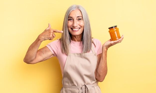 Симпатичная женщина среднего возраста, уверенно улыбаясь, указывая на собственную широкую улыбку. персиковое варенье