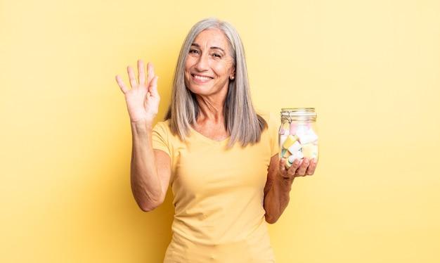 幸せに笑って、手を振って、あなたを歓迎して挨拶する中年のきれいな女性。キャンディーボトルのコンセプト