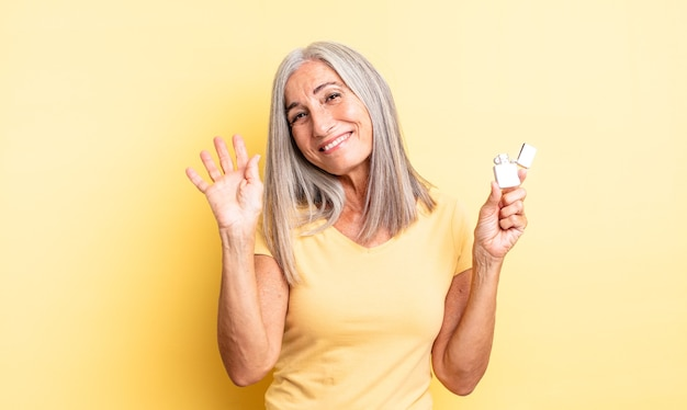Middle age pretty woman smiling happily, waving hand, welcoming and greeting you. lighter concept