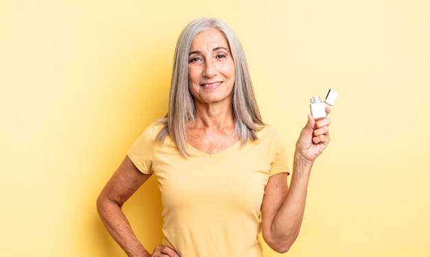 Middle age pretty woman smiling happily with a hand on hip and confident. lighter concept