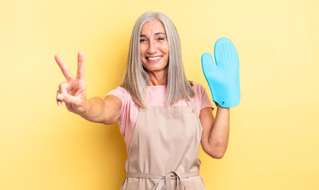 Middle age pretty woman smiling and looking happy, gesturing victory or peace. oven mitt concept