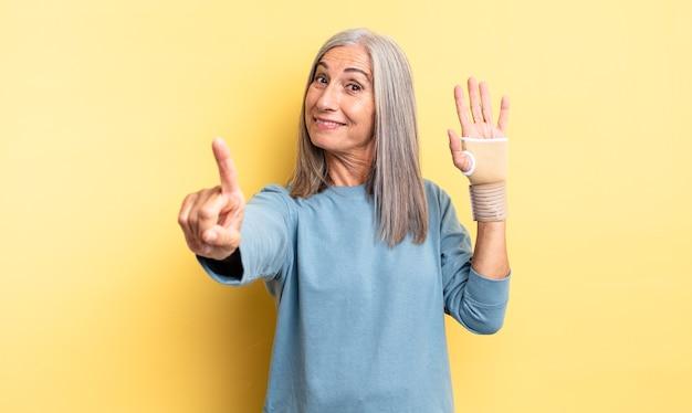 誇らしげにそして自信を持って笑顔でナンバーワンを作っている中年のきれいな女性。手の包帯の概念