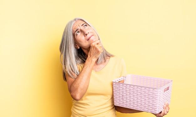 Симпатичная женщина среднего возраста думает, чувствует себя неуверенно и растерянно. концепция пустой корзины