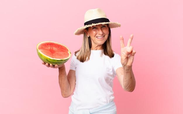 Среднего возраста красивая женщина с арбузом. летняя концепция