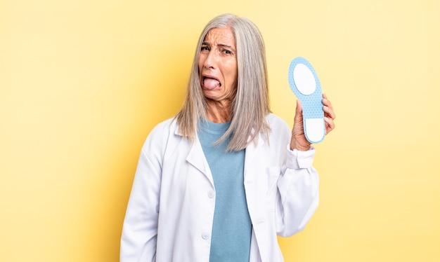 陽気で反抗的な態度、冗談を言ったり、舌を突き出したりする中年のきれいな女性。足病専門医の概念
