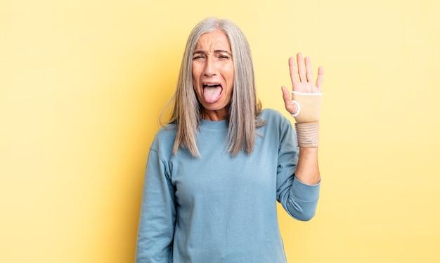 쾌활하고 반항적인 태도, 농담을 하고 혀를 내미는 중년의 예쁜 여자. 손 붕대 개념