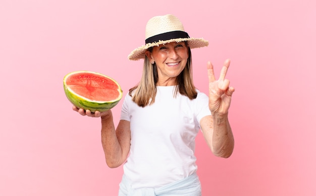 Middle age pretty woman with a watermelon. summer concept