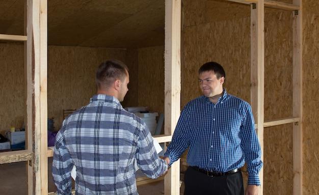 Мужчины среднего возраста профессиональные инженеры показывая рукопожатие на строительной площадке. подчеркивая одобренное проектное предложение.