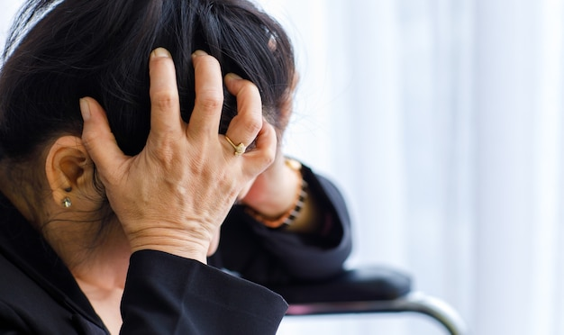 중년의 아시아 여성은 고통을 느끼고 갑작스러운 두통과 뇌졸증 발작을 일으키며 스트레스를 받은 얼굴로 머리를 감싸고 있습니다. 두뇌와 머리 문제의 개념입니다.