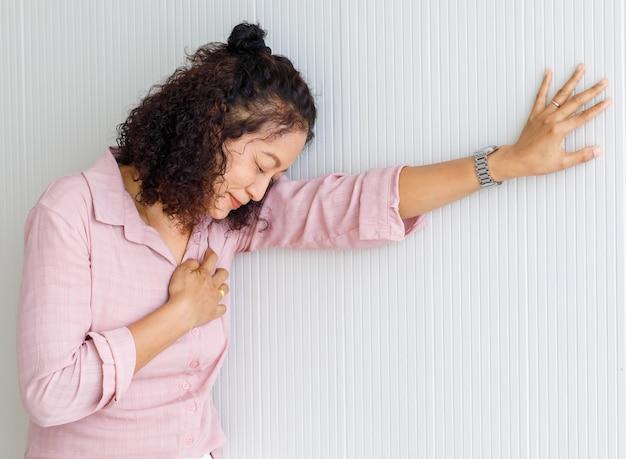 중년의 아시아 여성은 심장마비의 영향을 받아 움직임을 멈추고 벽에 기대어 있습니다.