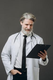 Среднего возраста старший врач мужчина держит буфер обмена над изолированной серой стеной