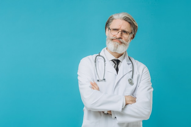 Человек доктора среднего возраста старший седой доктор нося медицинскую форму изолировал стену с серьезным выражением на стороне.
