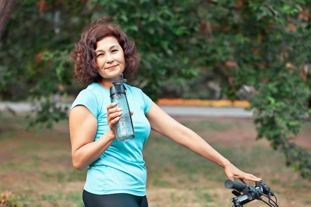 자전거를 탄 중년 여성은 야외 시골 공원에서 자전거를 타고 병에서 물을 마십니다.