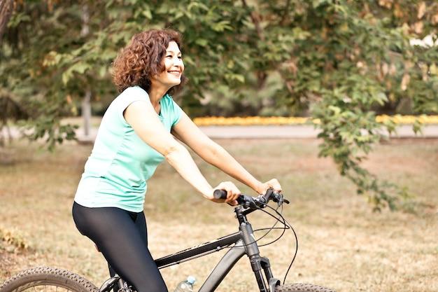 시골 공원 야외에서 자전거를 타는 중년 여성.
