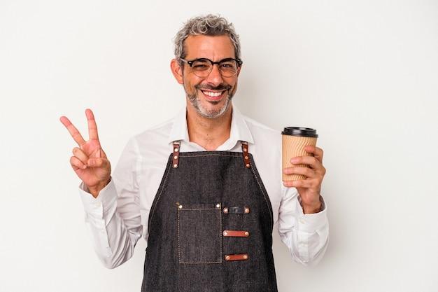 白い背景に分離された持ち帰り用のコーヒーを持っている中年の店員は、指で平和のシンボルを喜んで気楽に示しています。