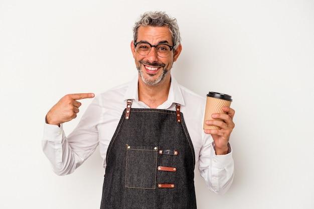 シャツのコピースペースを手で指している白い背景の人に分離されたテイクアウトコーヒーを保持している中年の店員、誇りと自信を持って