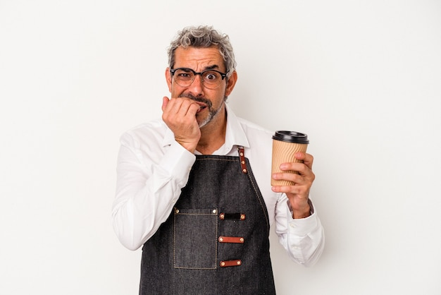 Middle age store clerk holding a take away coffee isolated on white background  biting fingernails, nervous and very anxious.