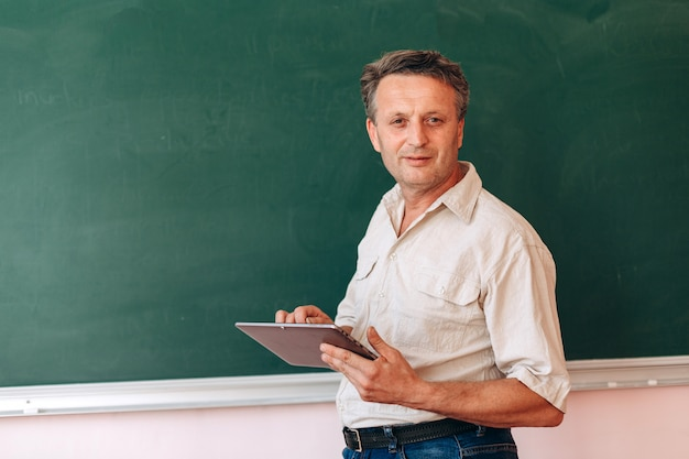 Middle age teacher next the blackboard holding an ipad and explain a lesson.