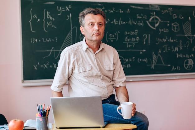Учитель среднего возраста, держа чашку, сидя рядом с открытым ноутбуком на столе.