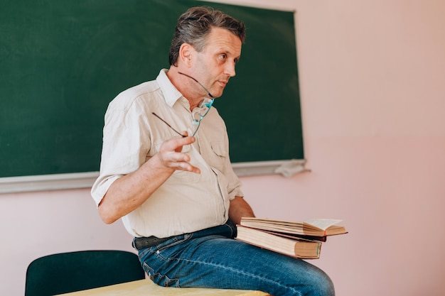 Middle age teacher holding a glasses and sitting with open textbook.