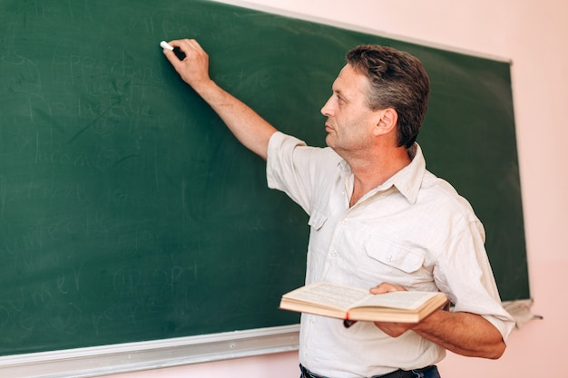 Middle age teacher write on the blackboard holding a textbook and explain a lesson.
