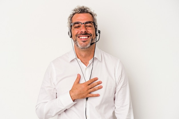 Middle age telemarketer caucasian man isolated on white background  laughs out loudly keeping hand on chest.