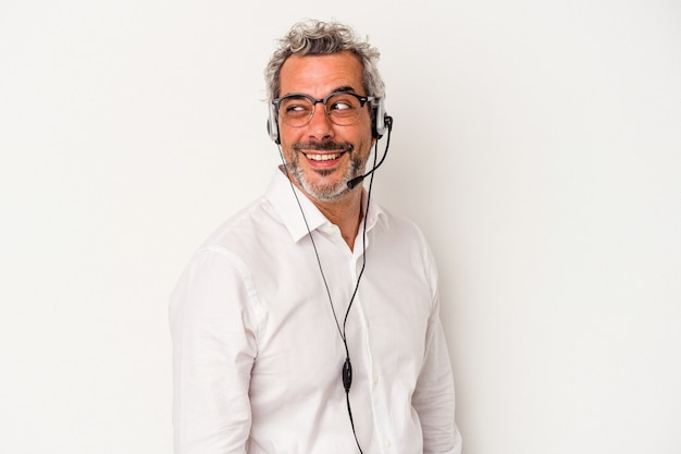 Middle age telemarketer caucasian man isolated on white background  looks aside smiling, cheerful and pleasant.